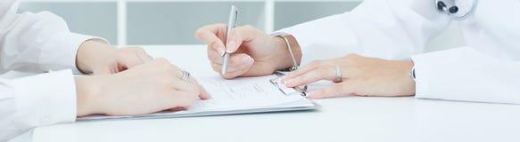 Врачуйте объяснять к ее женскому пациенту как заполнить медицинскую форму на офисе Как раз руки над таблицей Стоковое Фото