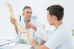 Врачуйте объяснять позвоночник к пациенту в офисе Стоковые Фото