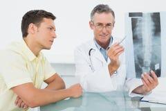 Врачуйте объяснять рентгеновский снимок позвоночника к пациенту в офисе Стоковое фото RF