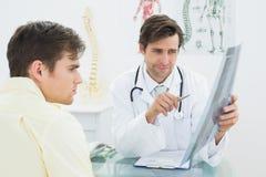 Врачуйте объяснять рентгеновский снимок позвоночника к пациенту в офисе Стоковые Изображения RF