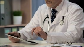 Врачуйте осматривая медицинский app на таблетке, нововведениях в обслуживаниях здравоохранения стоковое изображение rf