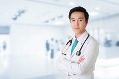 Врачуйте представлять при пересеченные оружия, медицинский персонал работая на расплывчатом стоковое изображение