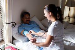 Врачуйте проверять кровяное давление старшей женщины в спальне Стоковое Изображение RF
