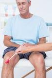 Врачуйте проверять отражения колена ее пациента Стоковая Фотография