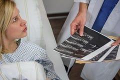 Врачуйте разговаривать с женским пациентом в больнице Стоковые Фотографии RF