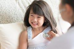 Врачуйте рассматривать азиатскую милую маленькую девочку путем использование стетоскопа стоковые изображения rf