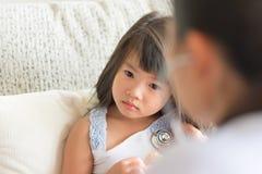 Врачуйте рассматривать азиатскую унылую маленькую девочку путем использование стетоскопа стоковые изображения rf