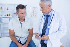 Врачуйте рассматривать его пациента и запись на доске сзажимом для бумаги стоковые фотографии rf