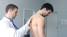 Врачуйте рассматривать назад молодого мужского пациента с стетоскопом акции видеоматериалы