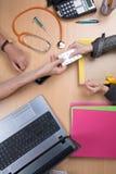 Врачуйте сидеть на столе и работу на компьтер-книжке получая пациента Стоковое Изображение