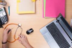 Врачуйте сидеть на столе и работу на компьтер-книжке получая пациента Стоковое Изображение RF