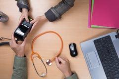 Врачуйте сидеть на столе и работу на компьтер-книжке получая пациента Стоковые Изображения