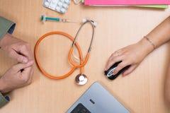 Врачуйте сидеть на столе офиса и получать пациента Стоковые Изображения