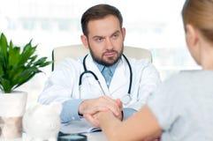 Врачуйте смотреть его пациента женщины пока говорящ к ей Стоковые Изображения