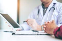 Врачуйте советовать с при пациент представляя результаты на цифровой плате стоковое изображение
