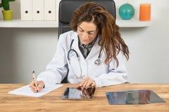 Врачуйте сочинительство женщины на бумаге смотря цифровую таблетку в офисе Стоковые Изображения