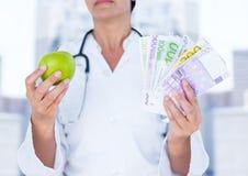 Врачуйте средний раздел с яблоком и деньги против расплывчатых зданий Стоковые Фото