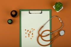 Врачуйте стетоскоп рабочего места оранжевый, таблетки, медицинские бутылки и пустую доску сзажимом для бумаги на оранжевой бумажн стоковые фото