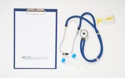 Врачуйте таблицу с медицинами, стетоскопом, доской сзажимом для бумаги и ручкой, взгляд сверху стоковые изображения rf