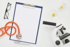 Врачуйте таблицу с микроскопом, стетоскопом и стеклами, взгляд сверху Стоковые Фотографии RF