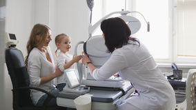 Врачуйте optometrist в клинике проверяя зрение ` s маленькой девочки - офтальмологию ` s детей Стоковые Изображения