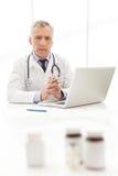 Врач. Зрелый доктор сидя на его месте службы с стоковые фото