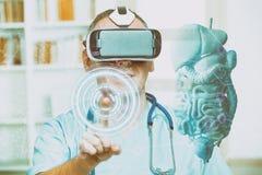 Врач используя шлемофон виртуальной реальности стоковое изображение