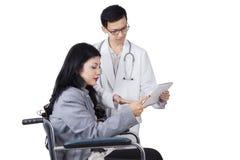 Врач и неработающая женщина держа таблетку стоковая фотография