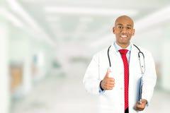 Врач показывая большие пальцы руки вверх стоя в прихожей больницы Стоковая Фотография RF