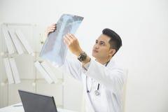 Врач смотря изображение рентгеновского снимка в офисе Стоковые Изображения RF