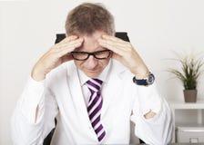 Врач страдая серьезную головную боль Стоковые Изображения
