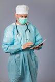 Врач с стетоскопом и лицевой щиток гермошлема держа таблетку Стоковая Фотография