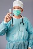 Врач с стетоскопом и лицевой щиток гермошлема держа шприц Стоковая Фотография
