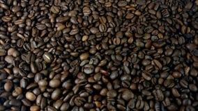 Вращая зажаренные в духовке коричневые кофейные зерна сток-видео