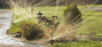 Вращая спринклер распыляя воду в задворк Стоковая Фотография RF
