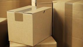 Вращение камеры над коричневыми как раз поставленными пакетами коробки коробки штабелированными на деревянном столе офиса готовом