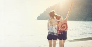 Временя, 2 девушки обнимая их шеи и поворачивая их задние части на пляже Стоковое Изображение RF