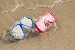 Временя: Красные и голубые gogles на песке океаном стоковые изображения