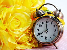 Время весны с предпосылкой букета будильника и искусственных цветков Стоковые Фотографии RF