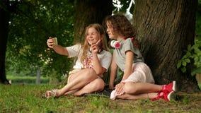 Время детства Милые усмехаясь маленькие девочки наслаждаясь в парке пока делающ Selfie и слушающ к музыке с чернью акции видеоматериалы