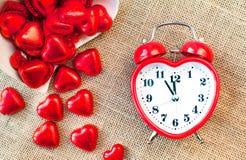 Время для влюбленности Часы красного сердца форменные с сладостными шоколадами Стоковое фото RF