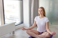 Время для йоги Привлекательная внушительная девушка сидя в положении лотоса йоги стоковая фотография rf