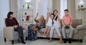 Время для сестры и брата видеоигры играя перед камерой пока бабушка и мать смотря их, детей видеоматериал