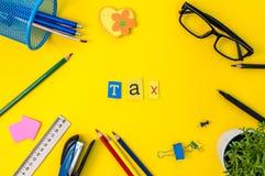 Время для тягл Финансовый учет денег Концепция обложения с suplies офиса на желтой предпосылке Стоковые Фотографии RF
