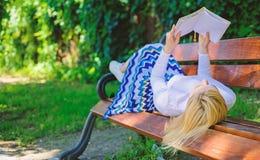 Время для улучшения собственной личности Женщина тратит отдых с книгой Дама наслаждается прочитать Девушка читая outdoors пока ос стоковые изображения rf