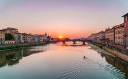Время захода солнца в Флоренсе, Италии Яркое небо над рекой Арно и средневековым мостом Стоковая Фотография RF