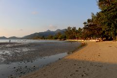 Время захода солнца на острове с предпосылкой голубого неба и горы Стоковые Фото