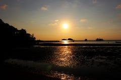 Время захода солнца на пляже с оранжевой предпосылкой неба Стоковая Фотография