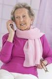 Время и концепция людей - близкая вверх счастливой старшей женщины с smartphone дома Стоковое Изображение