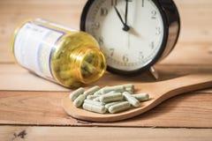 Время к медицинской капсуле с часами на деревянной таблице Стоковое Изображение RF